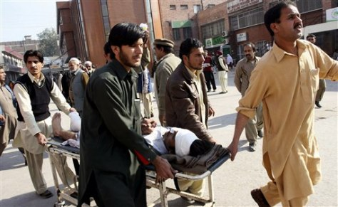 Image: Pakistani volunteers carry an injured person to a local hospital