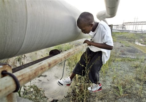 IMAGE: BOY PLAYS NEXT TO PIPE FROM OIL REFINERY
