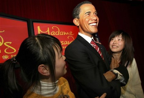 Image: People stand next to wax figure of Barack Obama