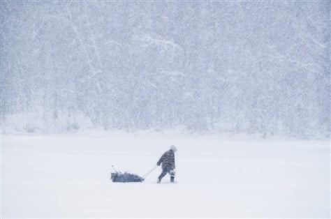 IMAGE: SNOW FALLS ON ICE FISHERMAN