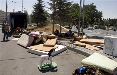 Image: Israeli workers unload the belongings of a Palestinian family in a street