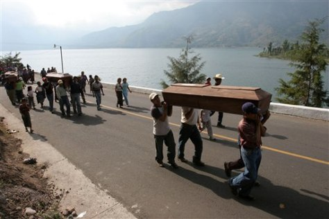 IMAGE: People carry coffins