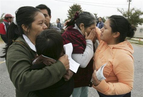 Image: Woman is comforted after raid