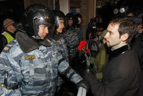 IMAGE: RUSSIAN RIOT POLICE GIVEN FLOWERS