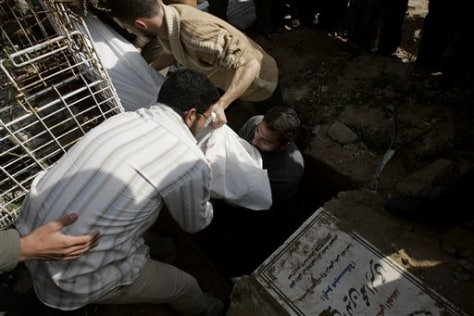 Image: Hisham Sarhi, center, helps lower the body of his cousin Kamel, 22, killed in an Israeli strike