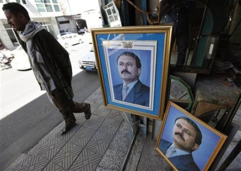 Image: Yemeni man passes pictures of president