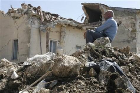 Image: Man sits in rubble in Onna, Italy