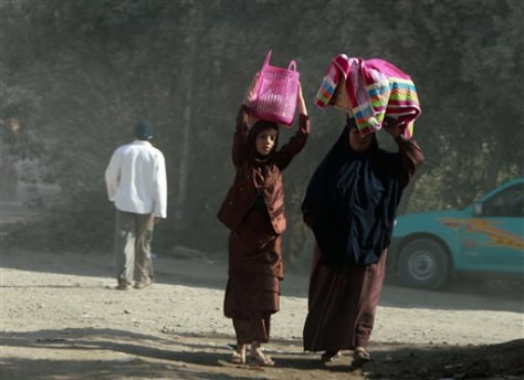 Image: Mother, daughter carry food for Eid al-Adha
