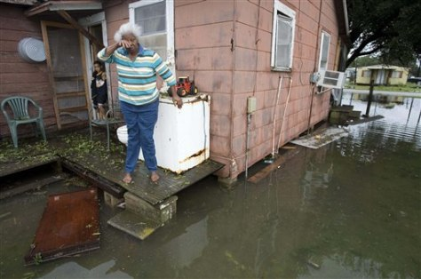 IMAGE: WOMAN NEXT TO FLOODED HOME
