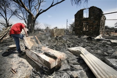 Image: Man sifts through burned out property