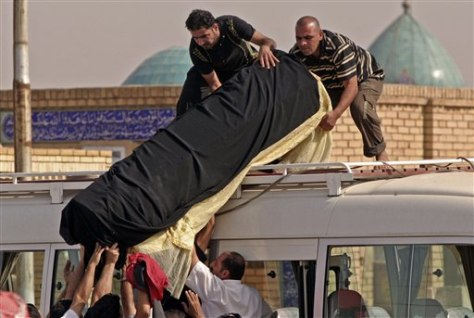 Image: Relatives and friends load coffin of Iraq bombing victim
