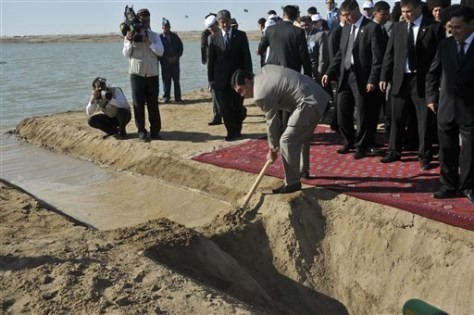 Image: Turkmen president helps dig breach to let water flow