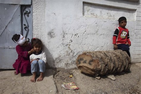 Image: Iraqi kids sit outside their home