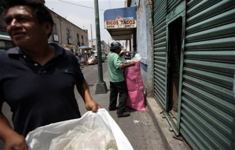 Image: Men collect plastic bags for recycling