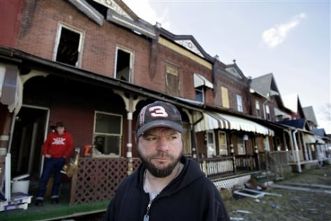 Image: Charles Thomas outside damaged house