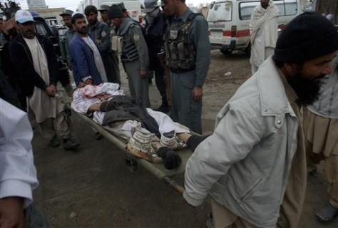 Image: Hospital workers carry the body of a suspected Taliban militant.