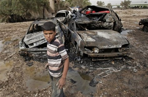 Image: A boy inspects a bombed car