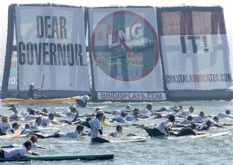 IMAGE: SURFERS AND PROTEST SIGN AGAINST NATURAL GAS PROJECT