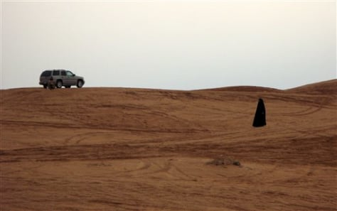 Image: Woman walks in desert.