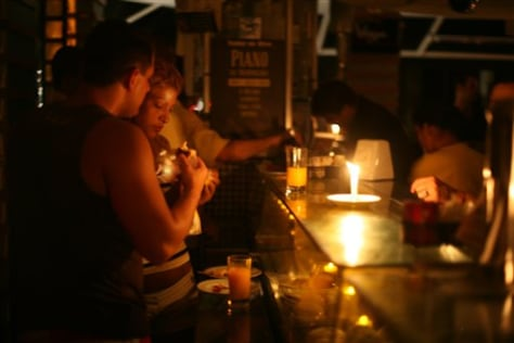 Image: People eat by candlelight at a restaurant in Rio