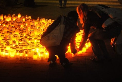 Image: People lay candles