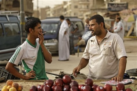 Image: Iraqis smoke in a market