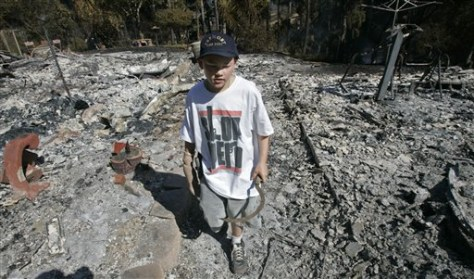 IMAGE: BOY WALKS THROUGH REMAINS OF HOME
