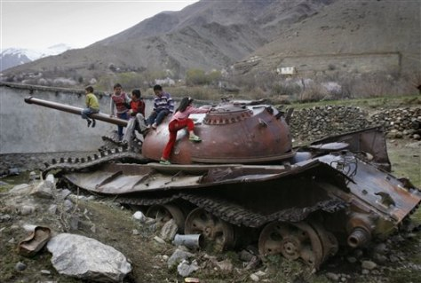 Image: Afghan children play on a destroyed tank