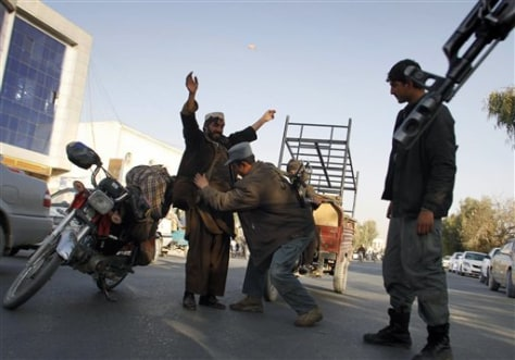 Image: Afghan policeman frisks man at a checkpoint in Kandahar