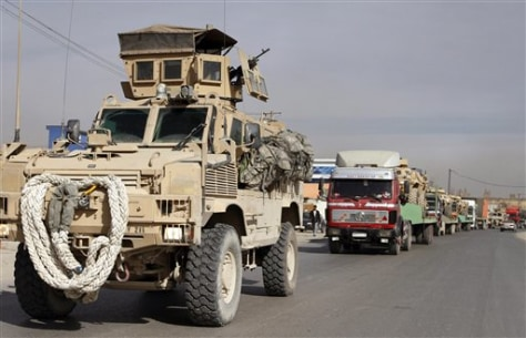 Image: U.S. armored personal carrier vehicle escorts a convoy of trucks