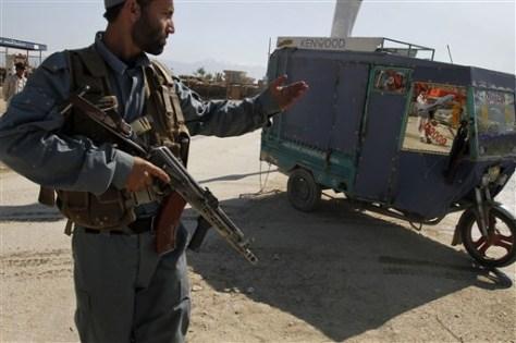 Image: An Afghan policeman stops a three-wheeler