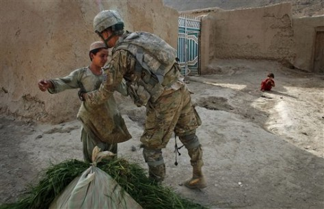 Image: Soldier searches a young boy