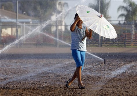 Image: A girl plays in the sprinklers