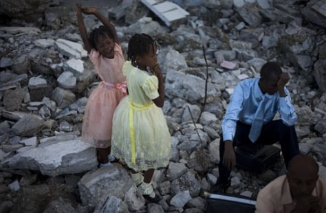 Catholics pray in the rubble of the Notre Dame cathedral in Port-au-Prince