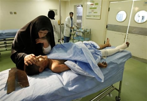 Image: Woman conforts son injured in Baghdad bombing