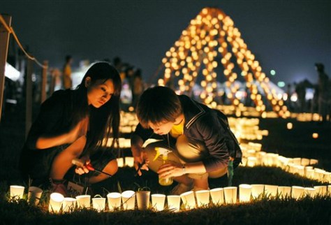 Image: Local residents light a candle at a park during a memorial event marking six months after the March 11 earthquake and tsunami