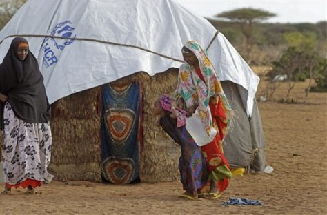 Image: A displaced woman lifts water off her child's back