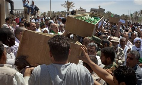 Image: Mourners carry coffins