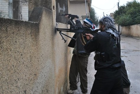 Image: Syrian rebels take their position behind a wall as they fire their guns during a battle with the Syrian government forces