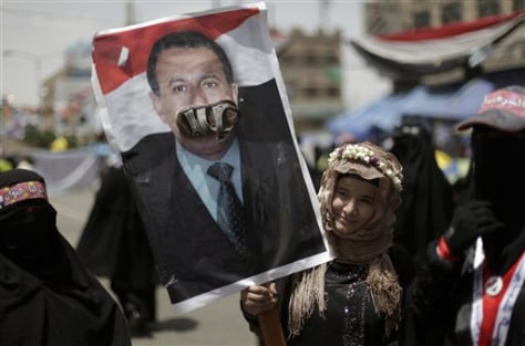 Image: A female anti-government protester holds up a poster of Yemeni President Ali Abdullah Saleh