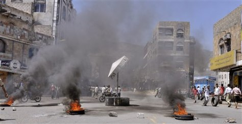 Image: Anti-government protesters block the road with rocks and burning tires