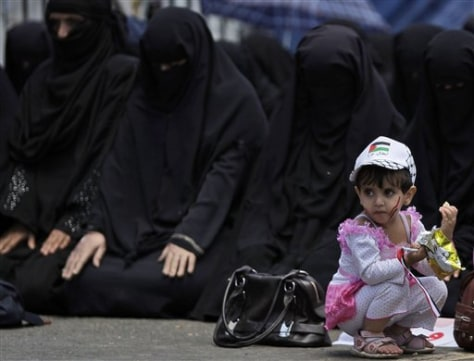 Image: A Yemeni girl in front of female anti-government protesters