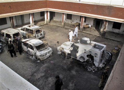 Image: Pakistani police officers examine damaged vehicles