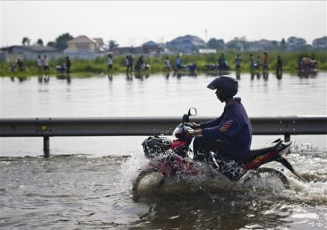 Image: A motorcyclist rides through a flooded road on the outskirts of Bangkok