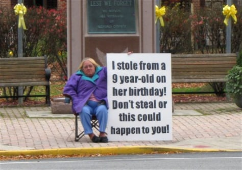 Image: Mom holds sign admitting theft