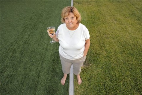 Image: Woman stands on artificial and natural grass