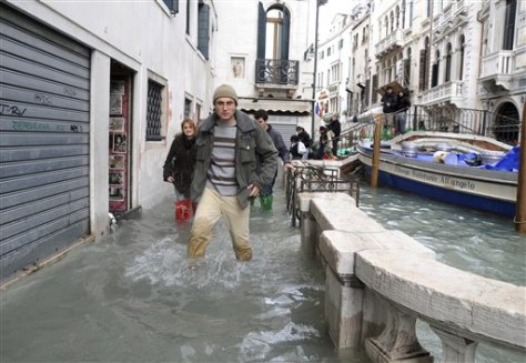Image: People wade through water in Venice