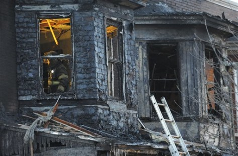 Image: Firefighters investigate the scene of an early morning fire