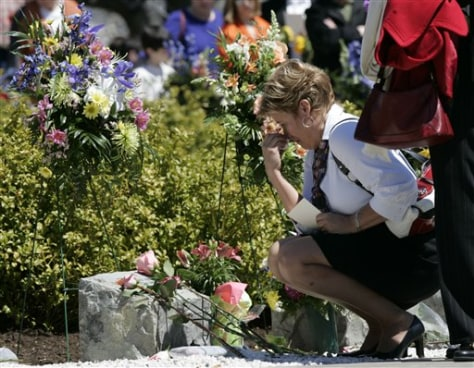 Image: Family member places flower on memorial marker