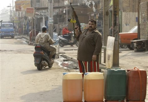 Image: An Iraqi gasoline street vendor holds up rifle